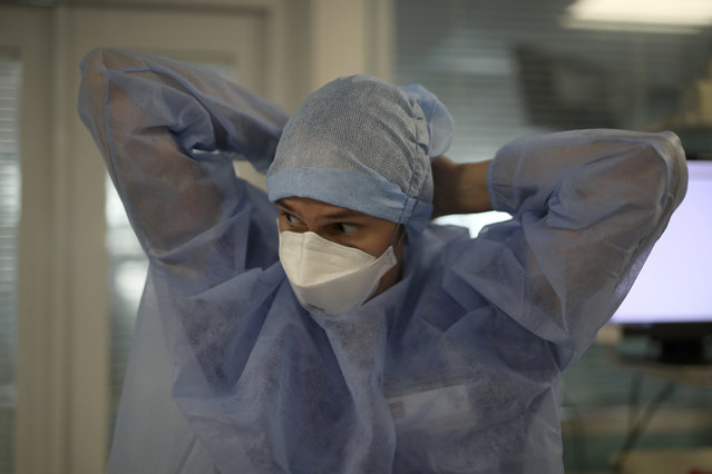 A nurse adjusts their suit in a COVID-19 area in a Marseille hospital, southern France, Thursday, September 10, 2020. As the Marseille region has become France's latest virus hotspot, hospitals are re-activating emergency measures in place when the pandemic first hit to ensure they're able to handle growing new cases. (Photo by Daniel Cole/AP Photo)