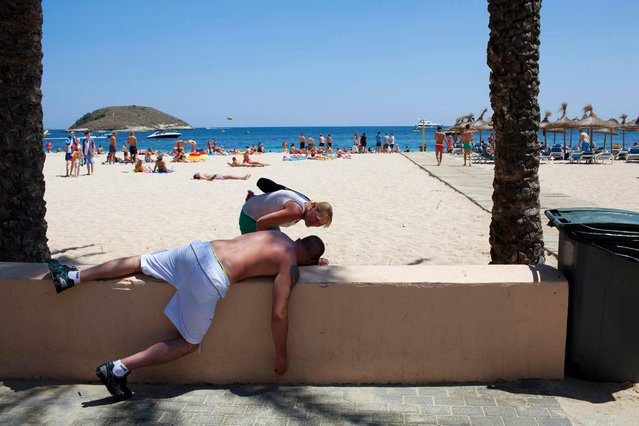 A Scottish woman checks on the well being of a British man slumped on a wall next to Magaluf beach, Majorca on June 29, 2013. (Photo by Peter Dench/Getty Images Reportage)