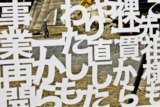 A worker walks behind a white plastic plate cutout of the words of a local businessperson, declaring determination to reopen the business, in a tsunami-stricken area in Minamisanriku, Miyagi prefecture, northern Japan, Monday, March 11, 2013. Japan marked the second anniversary on Monday of a devastating earthquake and tsunami that left nearly 19,000 people dead or missing. The words mean; I will restart my business from zero like my ancestor. (Photo by Shizuo Kambayashi/AP Photo)