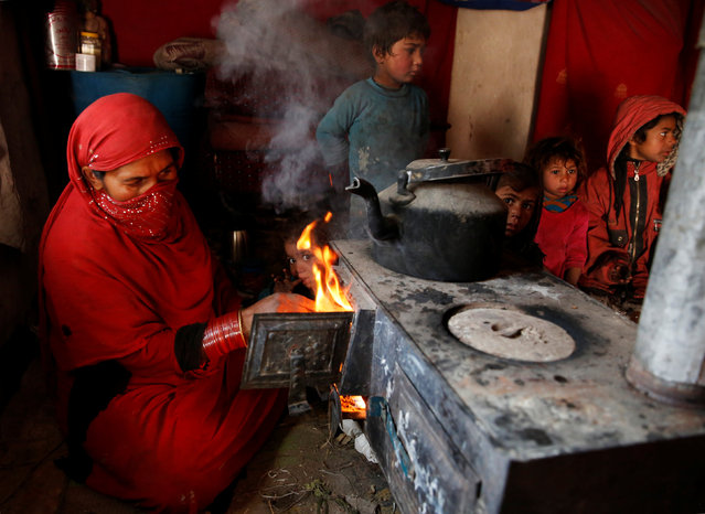 An internally displaced family warm themselves inside a shelter at a refugee camp in Kabul, Afghanistan January 30, 2018. (Photo by Mohammad Ismail/Reuters)