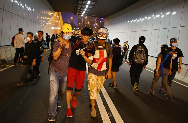 A pro-democracy protester reacts while walking in a tunnel during a rally close to the chief executive office in Hong Kong, November 30, 2014. (Photo by Bobby Yip/Reuters)