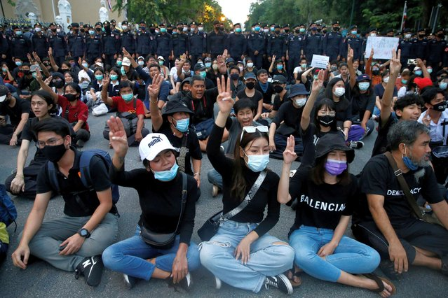 Pro-democracy demonstrators flash a three-finger salute while sitting on the ground during a Thai anti-government mass protest, on the 47th anniversary of the 1973 student uprising, in Bangkok, Thailand on October 14, 2020. (Photo by Soe Zeya Tun/Reuters)