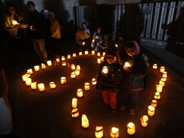 Children hold candles during Earth Hour after the lights were turned off in central Amman March 23, 2013. Earth Hour, when everyone around the world is asked to turn off lights for an hour from 8.30 p.m. local time, is meant as a show of support for tougher actions to confront climate change. (Photo by Ali Jarekji/Reuters)