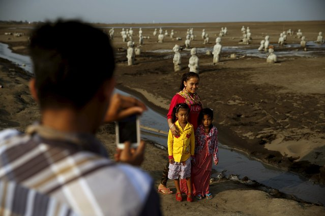 A man takes a picture of his family near stone sculptures of half-buried people at the Lapindo mud field in Sidoarjo, October 11, 2015. (Photo by Reuters/Beawiharta)