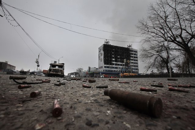 Shells and a burned police car are scattered on an empty square outside a burned-out publishing house in central Grozny, Russia, Thursday, December 4, 2014.  A gun battle broke out early Thursday in the capital of Russia's North Caucasus republic of Chechnya, puncturing the patina of stability ensured by years of heavy-handed rule by a Kremlin-appointed leader. The violence erupted hours before Russian President Vladimir Putin began his annual state of the nation address in Moscow. (Photo by Musa Sadulayev/AP Photo)