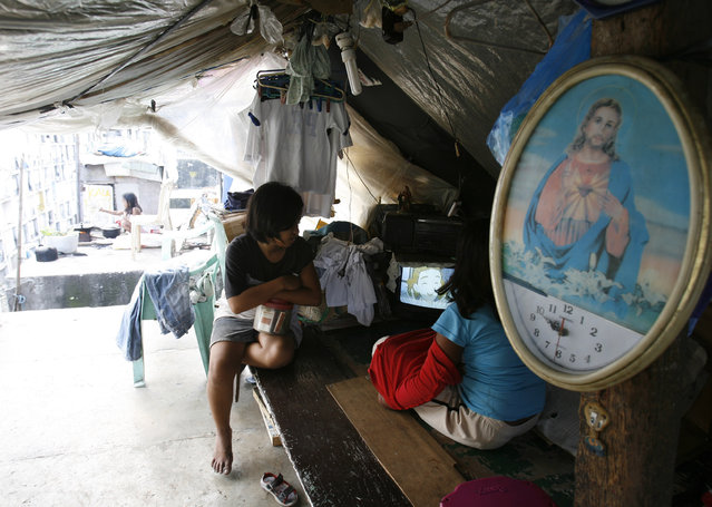 Residents watch television in their makeshift house atop gravestones inside a cemetery in Manila, October 21, 2008. (Photo by Cheryl Ravelo/Reuters)
