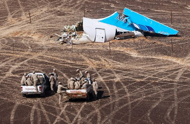 In this photo made available Monday, November 2, 2015, and provided by Russian Emergency Situations Ministry, Egyptian Military on cars approach a plane's tail at the wreckage of a passenger jet bound for St. Petersburg in Russia that crashed in Hassana, Egypt, on Sunday, Nov. 1, 2015. The Russian cargo plane on Monday brought the first bodies of Russian victims killed in a plane crash in Egypt home to St. Petersburg, a city awash in grief for its missing residents. (Photo by Maxim Grigoriev/Russian Ministry for Emergency Situations via AP Photo)