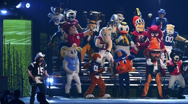 "Brad Paisley is accompanied by team mascots as he performs ""Country Nation"" at the 49th Annual Country Music Association Awards in Nashville, Tennessee November 4, 2015. (Photo by Harrison McClary/Reuters)"