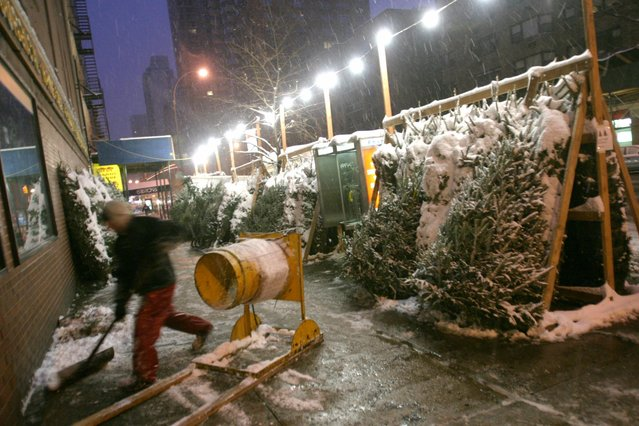 As dawn breaks, Daniel Deschenes clears snow from the sidewalk in front of a stand where he is selling Christmas trees in the Upper East side neighborhood of New York Saturday December 6, 2003. (Photo by Tina Fineberg/AP Photo)