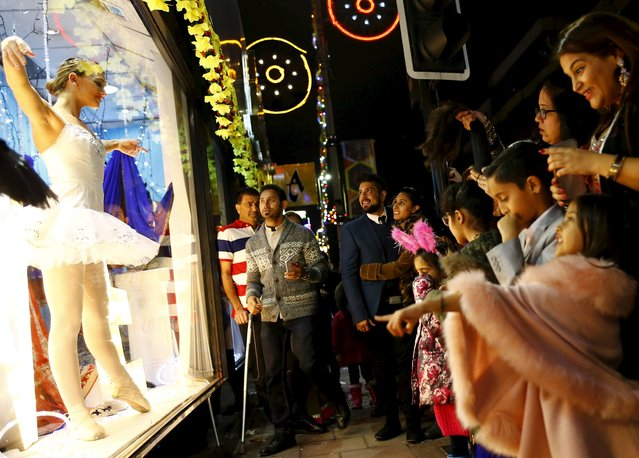 People watch a ballerina dance in a shop window during Diwali celebrations in Leicester, Britain November 11, 2015. (Photo by Darren Staples/Reuters)