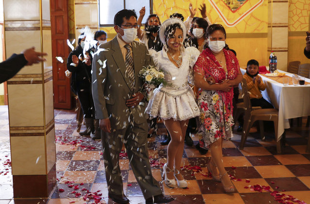 "Bride Ana Vallejos, wearing a traditional ""Caporales"" Andean outfit, is escorted by her parents to her wedding celebration, in La Paz, Bolivia, Saturday, December 12, 2020. As a measure to reactivate the economy, the Bolivian government lifted restrictions to help curve the spread of the new coronavirus. Sporting, religious and cultural events may take place publicly until mid-January. (Photo by Juan Karita/AP Photo)"