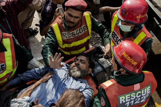 A victim is assisted by rescue workers at the site of the fire in Lahore. (Photo by Daniel Berehulak/Getty Images)