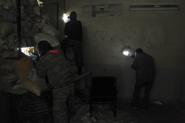 Rebel fighters take positions inside a room as they aim their weapons through holes in a wall in the old city of Aleppo near the frontline against forces loyal to Syria's President Bashar al-Assad December 28, 2014. (Photo by Jalal Al-Mamo/Reuters)