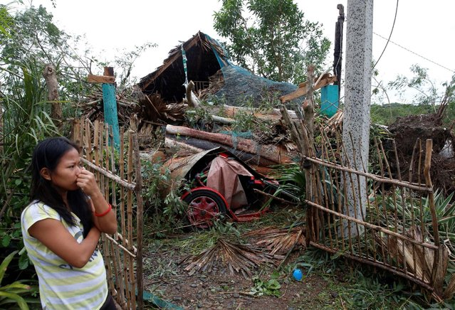 A woman stands outside her house which was damaged by a fallen tree during Typhoon Haima, in Bangui, Ilocos Norte in northern Philippines, October 20, 2016. (Photo by Erik De Castro/Reuters)