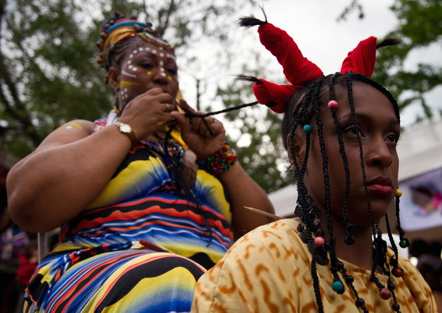 A woman has an Afro-Colombian hairstyle done during the 9th contest of Afro-hairdressers, in Cali, Valle del Cauca departament, Colombia, on May 12, 2013. The Afro hairstyles have their origins in the time of slavery, when women sat to comb their children hair after work. (Photo by Luis Robayo/AFP Photo)