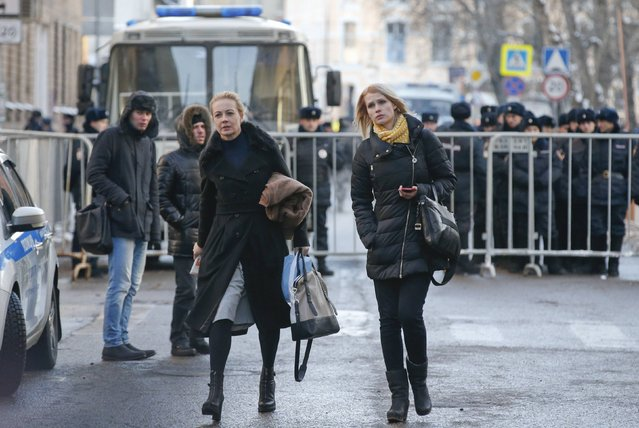 Yulia (L), wife of Russian opposition leader and anti-corruption blogger Alexei Navalny and Victoria, wife of Alexei's brother and co-defendant Oleg, walk past policemen after a court hearing in Moscow December 30, 2014. A Russian court ruled on Tuesday to give Kremlin critic Alexei Navalny a suspended sentence for embezzling money but jailed his brother for three and a half years in a case seen as part of a campaign to stifle dissent. (Photo by Tatyana Makeyeva/Reuters)