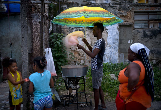 A street vendor prepares candy cotton for customers in Havana, Cuba, Wednesday, January 31, 2018. (Photo by Ramon Espinosa/AP Photo)