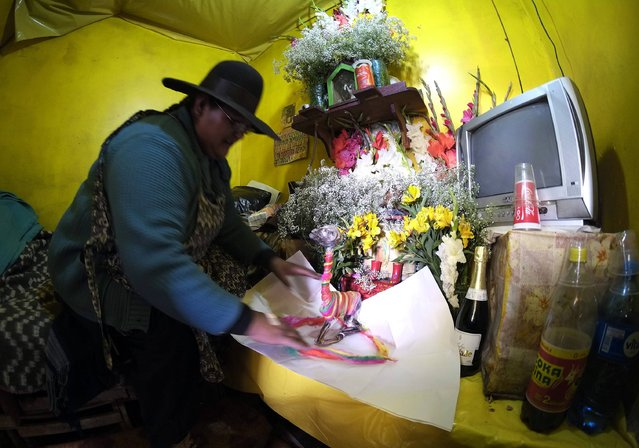 A female Aymara witchdoctor prepares an offering at the witches market of El Alto, on the outskirts of La Paz, December 31, 2014. (Photo by David Mercado/Reuters)