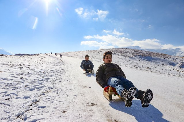 Children sledding down snowy hill in Gurpinar district of Turkey's Van province on December 20, 2020. (Photo by Mesut Varol/Anadolu Agency via Getty Images)