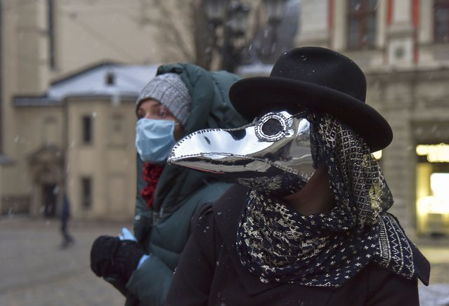 A woman wearing a protective mask is seen behind a girl dressed in a Plague Doctor Mask in Western-Ukrainian city of Lviv, Ukraine, 22 March 2020. Ukrainian Designer Anastasia Markovska sewed protective masks looking like Plague Doctor Masks, the traditional costume of Venice Carnival, for herself and her friends due to the ongoing pandemic of the COVID-19 disease caused by the SARS-CoV-2 coronavirus. In Ukraine had been 47 laboratory-confirmed cases of COVID-19, including three deaths and one recovery as Ukraine's Health Ministry announced. (Photo by Pavlo Palamarchuk/EPA/EFE)