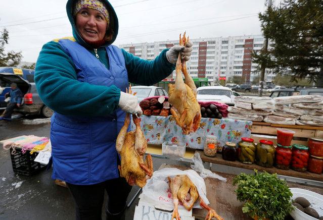 A foodstuff vendor reacts at a street market in Krasnoyarsk, Russia, October 17, 2016. (Photo by Ilya Naymushin/Reuters)