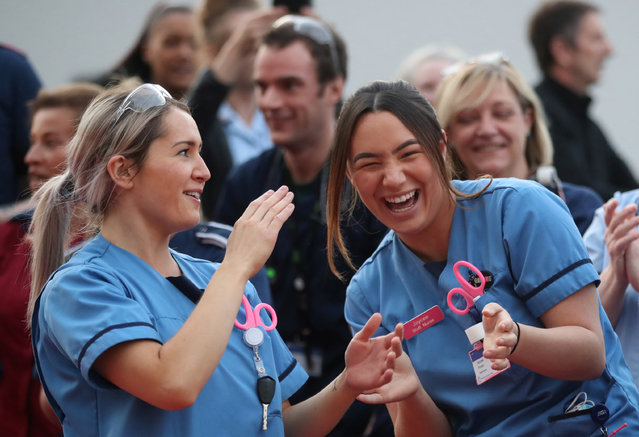 Medical staff react outside Queen Elizabeth Hospital during the Clap for our Carers campaign in support of the NHS, as the spread of the coronavirus disease (COVID-19) continues, in Birmingham, Britain, April 23, 2020. (Photo by Carl Recine/Reuters)