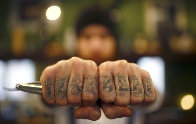"Alex ""Torreto"" Vellios, a 26-year old barber displays his tattoo reading ""barber"" as he waits for his first customer of the day at his Torreto barber shop in Frankfurt January 6, 2015. (Photo by Kai Pfaffenbach/Reuters)"