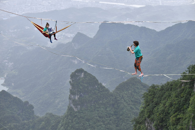 Members of performing group Houle Douce practise their instruments on tightropes ahead of a performance, at the Tianmen Mountain National Park in Zhangjiajie, Hunan province, China May 23, 2018. (Photo by Reuters/China Daily)