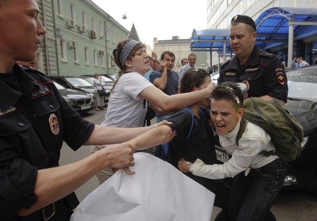 """A radical Orthodox believer (C) crushes an egg on a gay rights activist during a protest against a proposed new law termed by the State Duma as """"against advocating the rejection of traditional family values"""" in central Moscow June 11, 2013. Russian police detained more than 20 gay rights activists involved in a """"kissing protest"""" on Tuesday outside parliament where lawmakers were preparing to pass a bill banning homosexual """"propaganda"""". (Photo by Maxim Shemetov/Reuters)"""