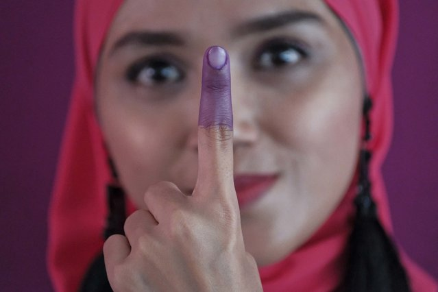 A Malaysian Muslim woman shows her inked finger after casting her ballot during the voting day of general elections in Kuala Lumpur, Malaysia, Wednesday, May 9, 2018. Voting has begun in a fiercely contested Malaysian election that pits a reunited opposition led by former authoritarian leader Mahathir Mohamad against the ruling coalition of Prime Minister Najib Razak whose image has been sullied by corruption allegations and an unpopular goods and services tax. (Photo by Sadiq Asyraf/AP Photo)