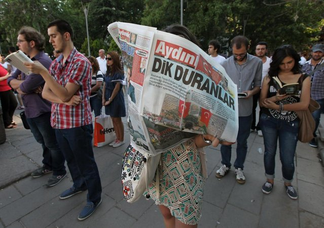 "A woman reads a newspaper with the headline reading ""Standing men"", during a silent protest in Guven Park in Ankara, Turkey, Wednesday, June 19, 2013. After weeks of sometimes-violent confrontation with police, Turkish protesters have found a new form of resistance, standing still and silent. (Photo by Burhan Ozbilic/AP Photo)"