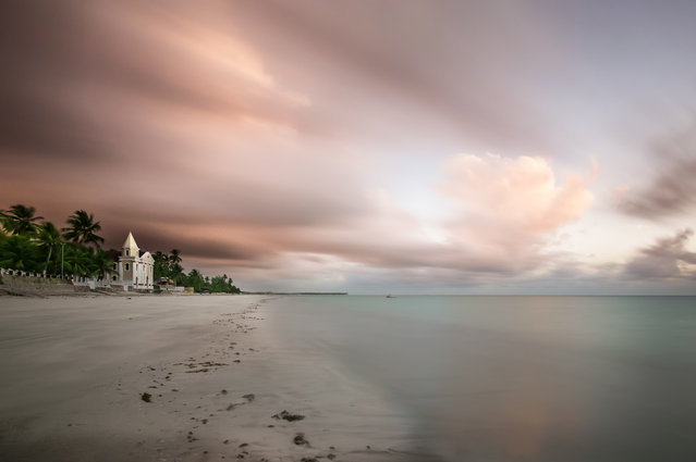"""Churh by the ocean"". Morning in Pernambuco, Northeastern Brazil. This charming and fantastic church of São Pedro, was laying at the ocean, a calm and serene scene. Wind was blowing fast, so I decided to show the cloud movement using a ND filter. (Photo and caption by Dante Laurini/National Geographic Traveler Photo Contest)"