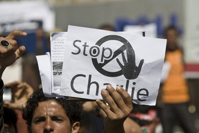 A Yemeni man holds a poster, while chanting slogans during a protest against caricatures published in French magazine Charlie Hebdo in front of the French Embassy in Sanaa, Yemen, Saturday, January 17, 2015. (Photo by Hani Mohammed/AP Photo)