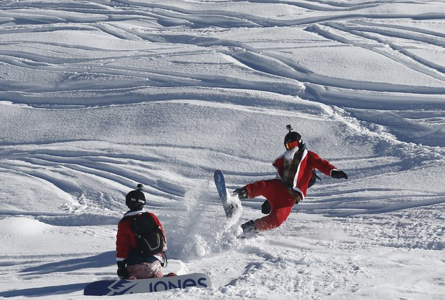 A man, dressed as Santa Claus, falls on his snowboard during a promotional event on the opening weekend in the alpine ski resort of Verbier, Switzerland, December 6, 2015. (Photo by Denis Balibouse/Reuters)