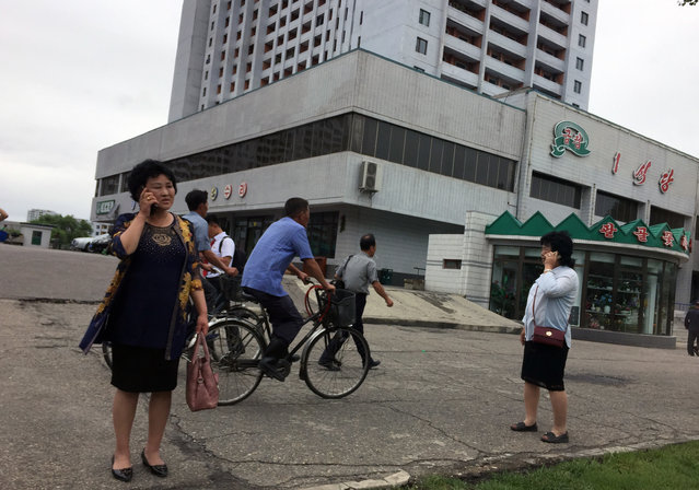 Residents go about their business near one of the city's biggest department stores and shopping areas in Pyongyang, North Korea Sunday, June 10, 2018. Despite the focus of world attention on the upcoming summit in Singapore between US President Donald Trump and North Korean leader Kim Jong Un, many North Koreans remain in the dark about what is happening outside their isolated nation. (Photo by Eric Talmadge/AP Photo)