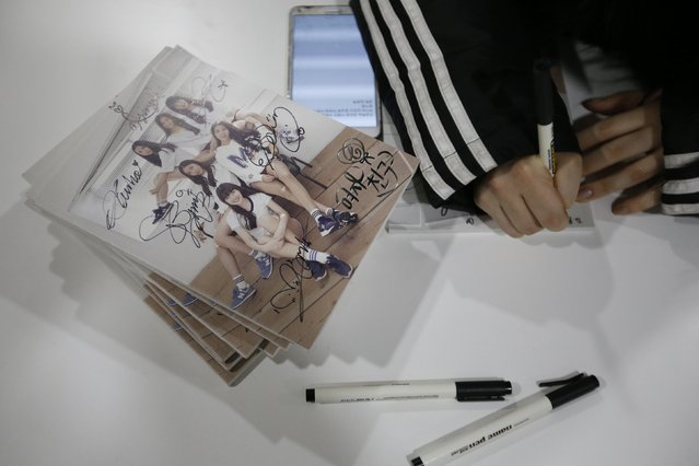 "A member of South Korean girl group GFriend signs her autograph on their album as they rest before ""The Show"" in Seoul January 20, 2015. (Photo by Kim Hong-Ji/Reuters)"