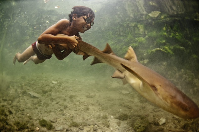 """Enal with Pet Shark"". Enal, a young sea nomad, rides on the tail of a tawny nurse shark, in Sulawesi, Indonesia. Marine nomadism has almost completely disappeared in South East Asia as a result of severe marine degradation. I believe children such as Enal have stories that could prove pivotal in contemporary marine conservation. (Photo and caption by James Morgan/National Geographic Traveler Photo Contest)"