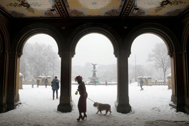 A woman walks a dog through the Bethesda Terrace in Central Park as heavy snow falls in Manhattan, New York City, U.S., February 7, 2021. (Photo by Andrew Kelly/Reuters)