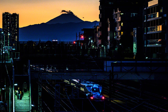 """This picture taken on February 4, 2021 shows a """"shinkansen"""", or high speed bullet train, N700A series, leaving Tokyo at dusk as Mount Fuji, Japan's highest mountain at 3,776 meters (12,388 feet), looms in the distance. (Photo by Charly Triballeau/AFP Photo)"""