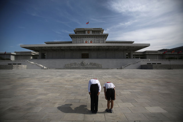 Two North Korean schoolchildren bow and pay respects to their late leaders Kim Il Sung and Kim Jong Il whose bodies lie embalmed in the mausoleum, the Kumsusan Palace of the Sun, on Thursday, July 25, 2013 in Pyongyang, North Korea. (Photo by Wong Maye-E/AP Photo)