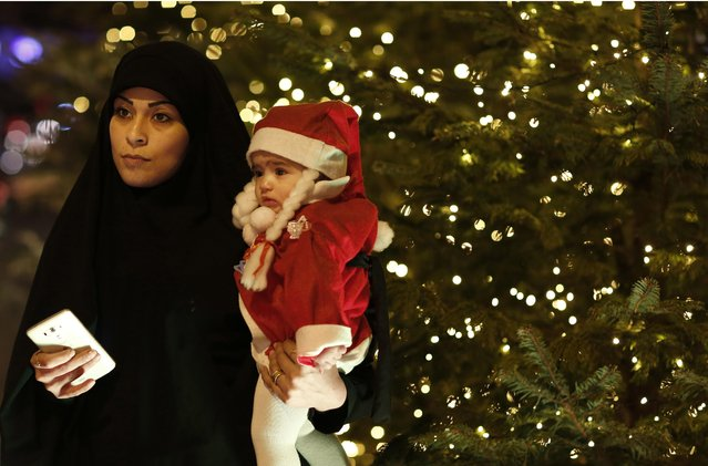 A Lebanese Shiite woman waits with her daughter to takes a picture with Santa Claus in front a Christmas tree in Downtown Beirut, Lebanon, Thursday, December 24, 2015. (Photo by Hassan Ammar/AP Photo)
