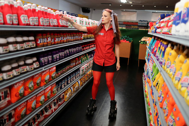 British artist Lucy Sparrow, adjusts bottles of ketchup in a art installation supermarket in which everything is made of felt, in Los Angeles, California on July 31, 2018. (Photo by Lucy Nicholson/Reuters)