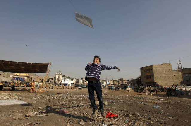 Eight-year-old Aayan helps his friend to fly a kite along a littered ground near a low income residential area in Karachi, Pakistan, December 20, 2015. (Photo by Akhtar Soomro/Reuters)