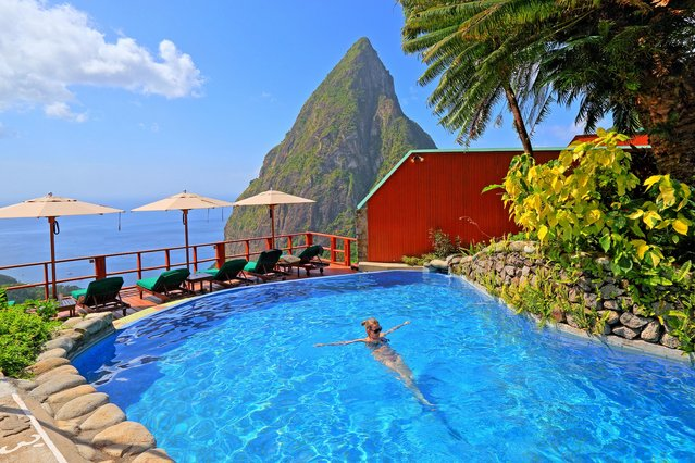 World's Greatest Swimming Pools: Ladera Resort swimming pool with the Petit Piton 743m, Soufriere, St. Lucia, Lesser Antilles, West Indies, Caribbean Islands. In full view of the Caribbean island's only UNESCO World Heritage site – the imposing, craggy Piton mountains – each of the 37 suites in this rainforest oasis welcomes guests with a private plunge pool. There's also a stunning communal watering hole (pictured). Some suites even have swings that dangle invitingly over their pools. By night, stargaze and listen to nature's foamy spew and metronomic chirps. (From $560). (Photo by Alamy Stock Photo)