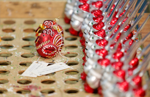 """Painted glass Christmas and New Year decorations depicting a rooster which is related to the 2017 Chinese Lunar New Year, are pictured at the """"Yolochka"""" (Christmas tree) factory, which has been producing glass decorations and toys for the festive season since 1848, in the town of Klin outside Moscow, Russia, November 24, 2016. (Photo by Maxim Zmeyev/Reuters)"""
