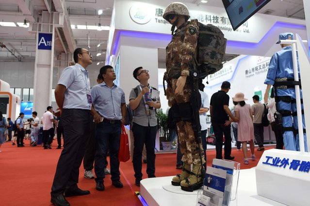 A group of men look at a exoskeleton robot at the 2018 World Robot Conference in Beijing on August 15, 2018. (Photo by Wang Zhao/AFP Photo)