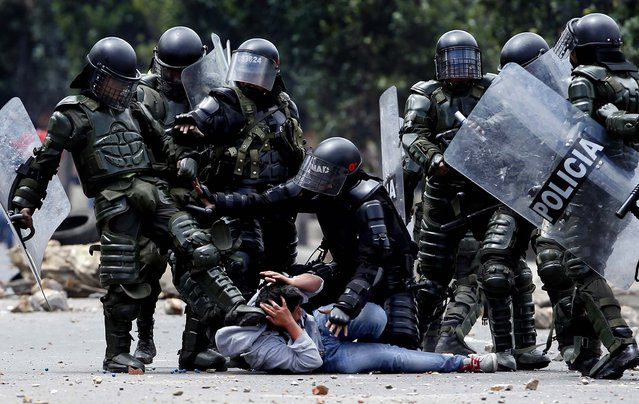 A police officer kicks a protester as another, tries to protect him before his arrest during protests in Ubate, north of Bogota, Colombia, on August 26, 2013. Hundreds of protesters clashed with police in support of farmers who have being blockading Colombian highways for a week for an assortment of demands that include reduced gasoline prices, increased subsidies and the cancellation of free trade agreements. (Photo by Fernando Vergara/Associated Press)