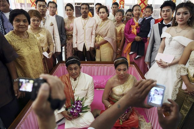 Grooms and brides pose inside and around a pink coffin after their wedding ceremony at Wat Takien temple in Nonthaburi province, on the outskirts of Bangkok February 14, 2015. (Photo by Damir Sagolj/Reuters)