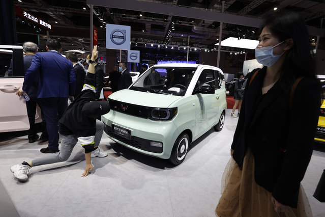 A man uses his arms to compare to the mini size of the GM's Wuling joint venture electric Macaron during the Shanghai Auto Show in Shanghai on Monday, April 19, 2021. (Photo by Ng Han Guan/AP Photo)