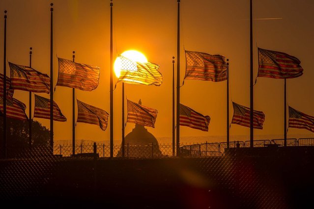 Flags surrounding the Washington Monument fly at half-staff as ordered by President Barack Obama following the deadly shooting at the Washington Navy Yard, on September 17, 2013. (Photo by J. Scott Applewhite/Associated Press)